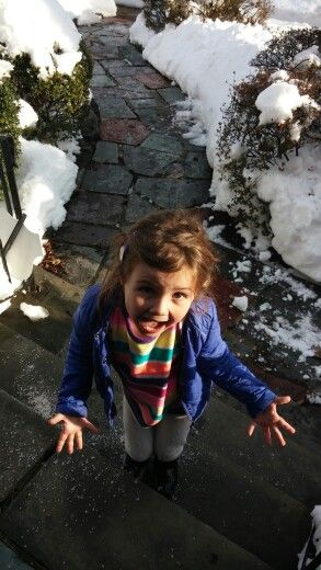little girl on steps surrounded by snow